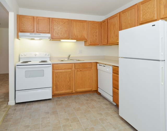 Boothwyn Court Sample Kitchen with Wood Cabinets and White Appliances | Apartments in Garnet Valley, PA