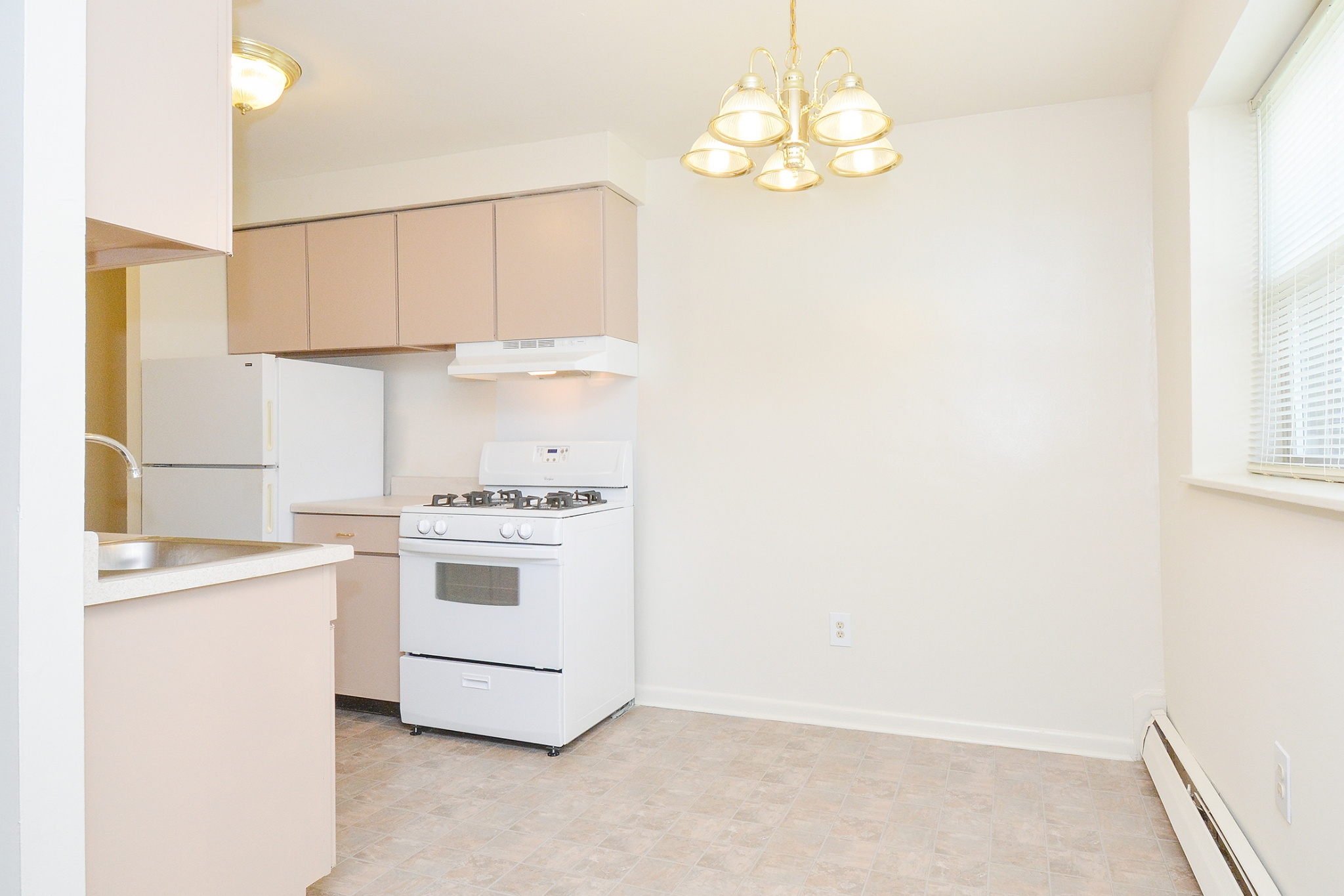 Newport Village Sample Dining Room with Chandelier and white Appliances | Levittown PA Apartments