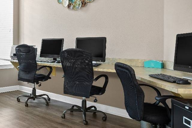 Business Center Workspaces with Computers and Office Chairs
