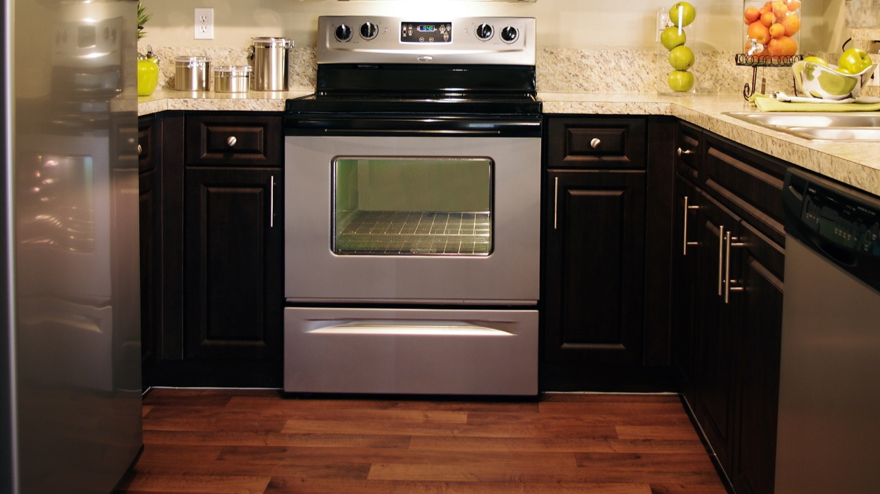 View of stainless-steel oven and stove in enclosed apartment kitchen featuring dark wood cabinets and granite countertops. Oven includes storage drawer. Stainless double sink and wood plank flooring