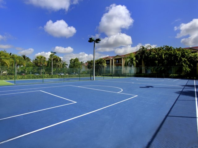 Large fenced-in community tennis court and badminton court