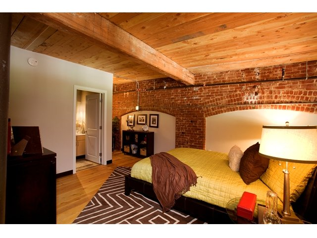 Cozy bedroom with bed tucked against exposed brick wall. Exposed beam ceiling and hardwood flooring with en suite bathroom.