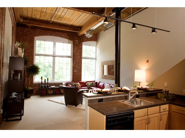 Apartment interior view with corner of kitchen and high-top counter visible in foreground. Living room with oversized windows, exposed brick and 16\' ceiling with exposed beams in background.
