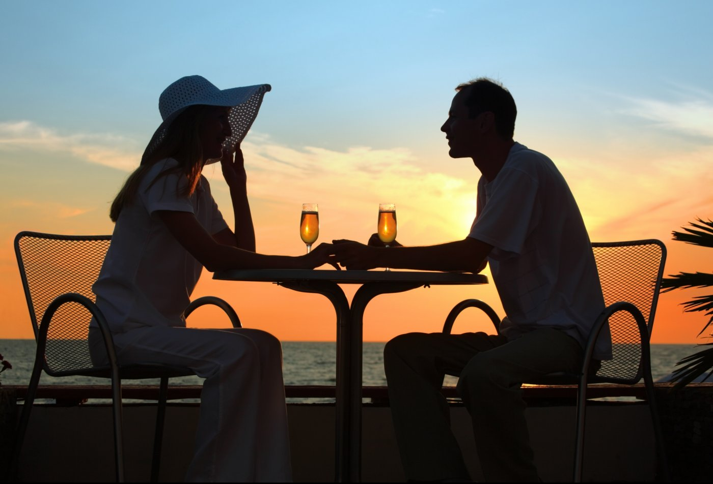 Couple enjoying dinner outside during the Key West sunset drinking champagne.