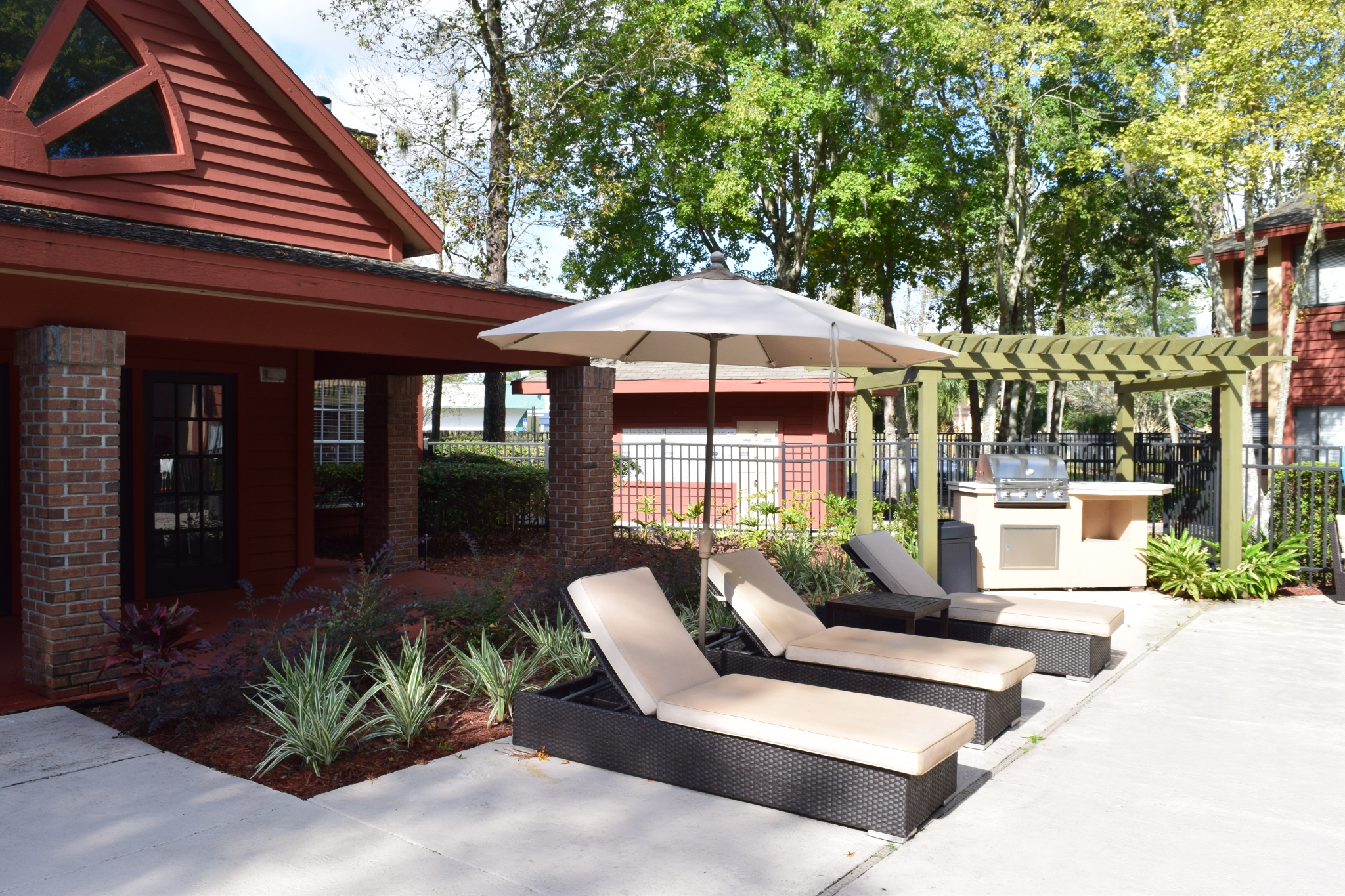 Deerfield Apartments view of padded modern lounge chairs under umbrella next to a gazebo with an outdoor grill