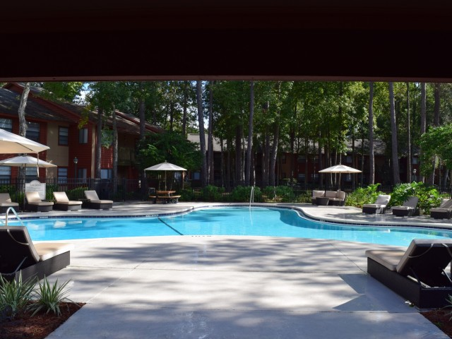 Deerfield Apartments swimming pool with modern lounge chairs and umbrellas