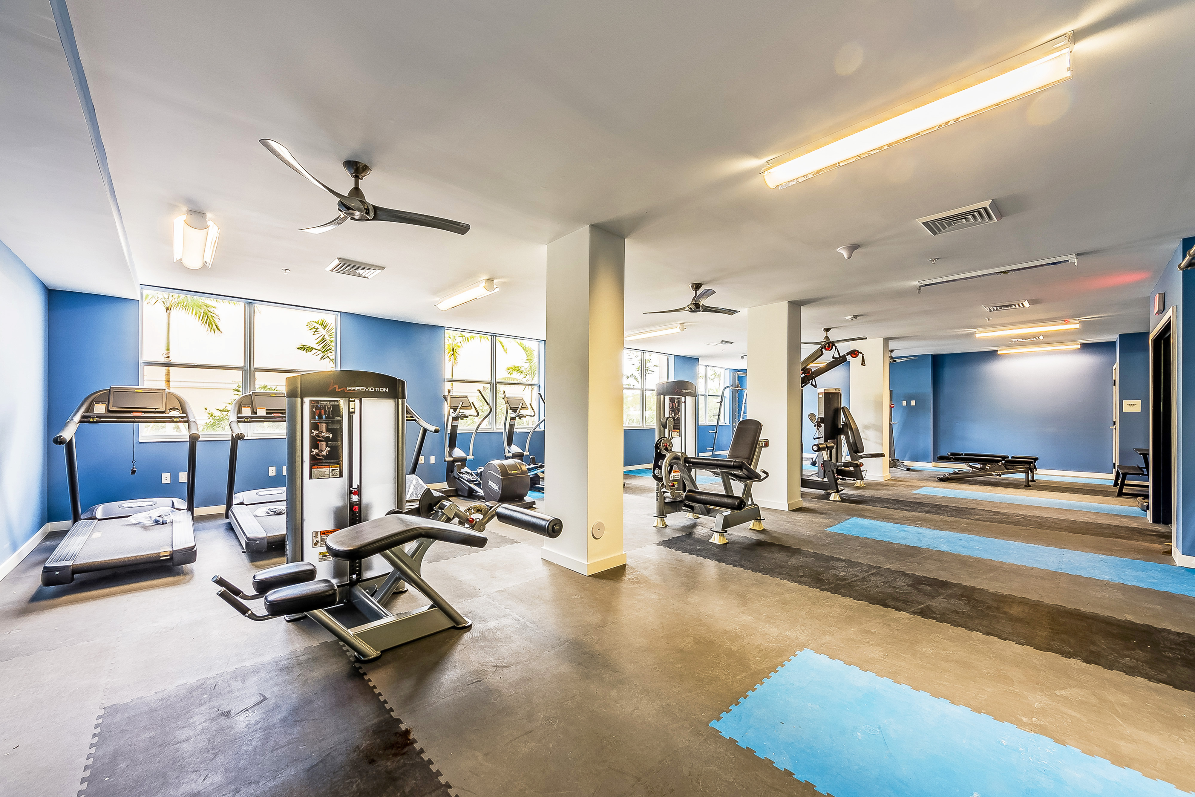 Fitness center with treadmills, workout benches, and various weight machines