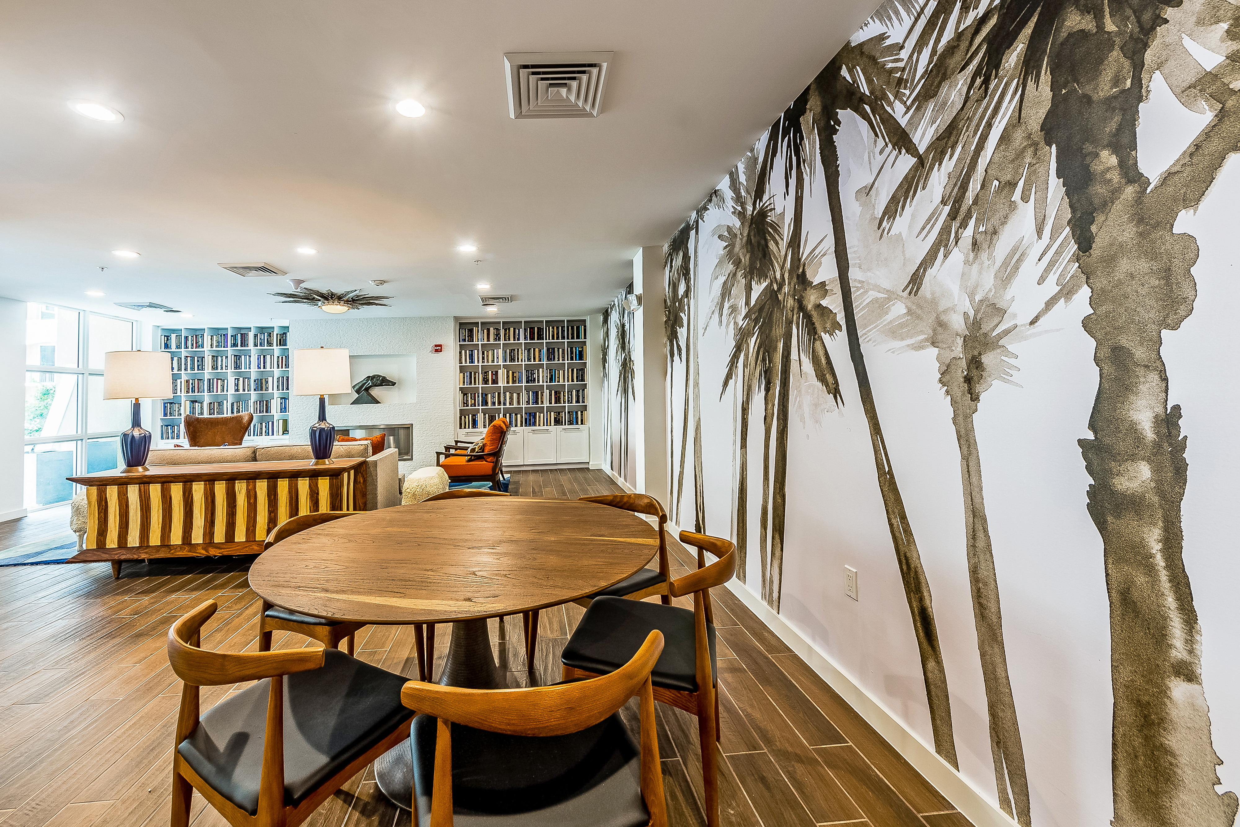 Clubhouse lounge with large round table, seating around a fireplace, bookshelves, and a wall mural of palm trees