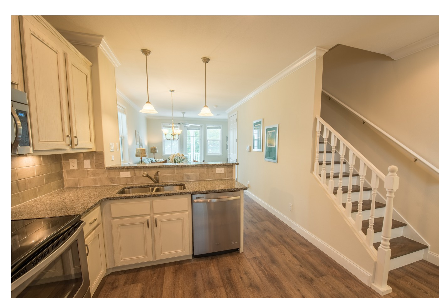 Multiple Level Apartment Home model showing beach style hard wood flooring and white staircase to the 2nd level.