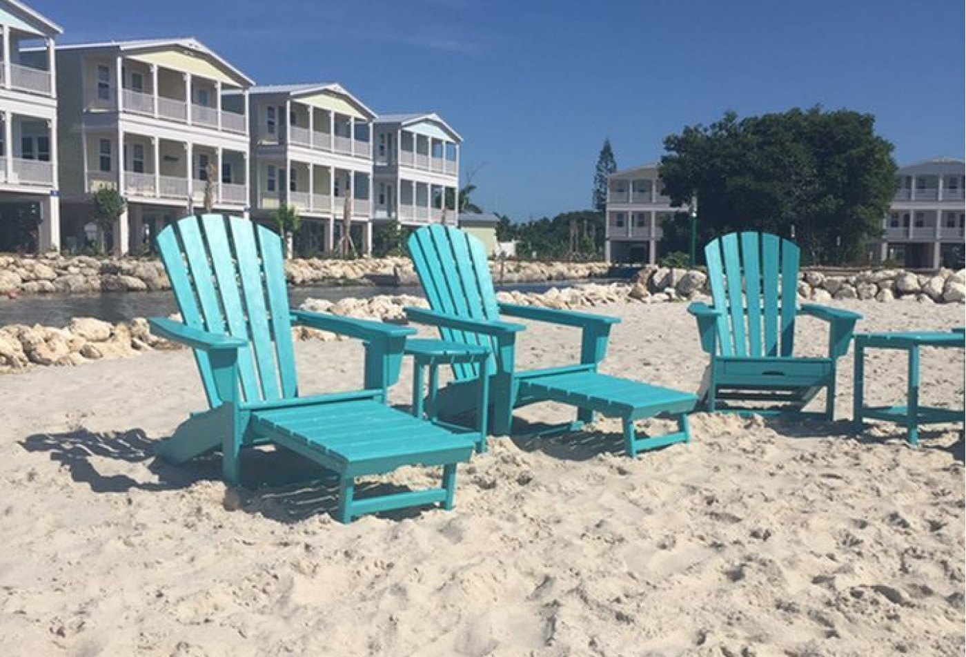 Blue adirondack chairs seating looking out over the ocean.