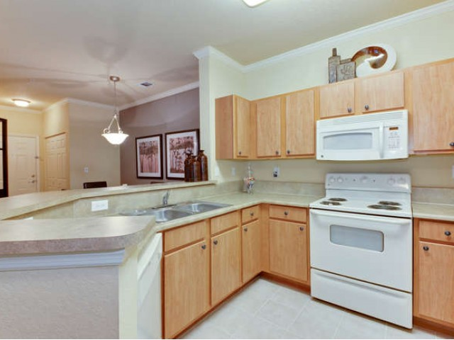 Eastport Apartments kitchen with wooden cabinetry, dishwasher, built-in microwave and range