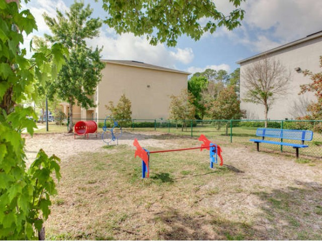 Eastport Apartments fenced pet park with agility equipment and bench