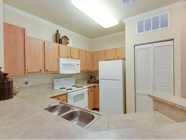 Eastport Apartments view of kitchen from dining room including appliances and a pantry