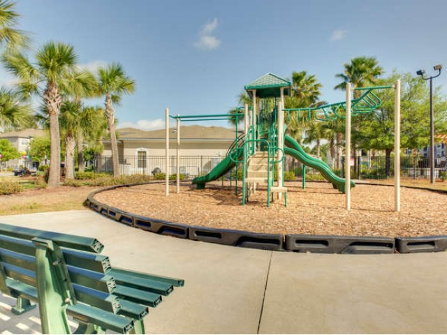 Eastport Apartments Community Playground with play equipment and bench