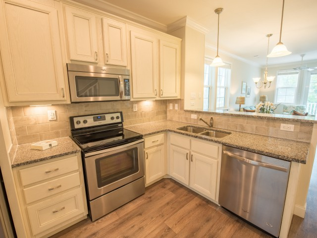 Beautiful kitchens with stainless steel appliances, pendant lighting, granite countertops, white cabinetry and nickel fixtures l Tarpon Harbour