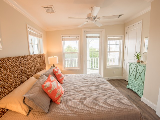 Bedroom with large bed and furniture with ceiling fan l Tarpon Harbour