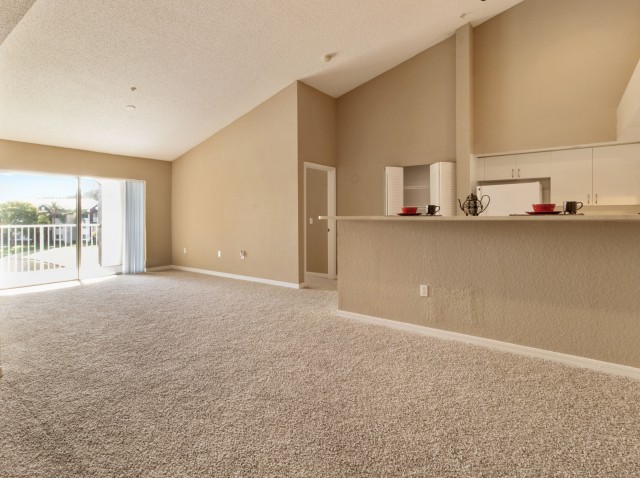 Unfurnished apartment interior featuring open living area connected to kitchen with tall countertops, patio accessible from living room.