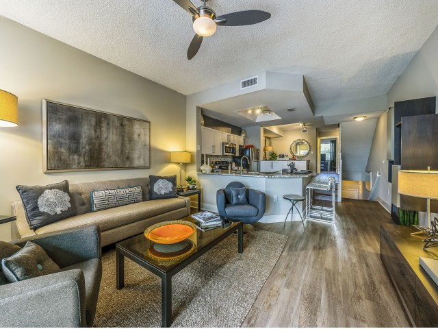 Living room with wood  flooring, large couch, coffee table and chairs looking into kitchen with stainless steel appliances, granite counters and bar seating with stairs leading down to entrance