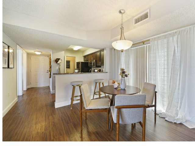 Dining room with table and four chairs looking into kitchen with bar and two stools