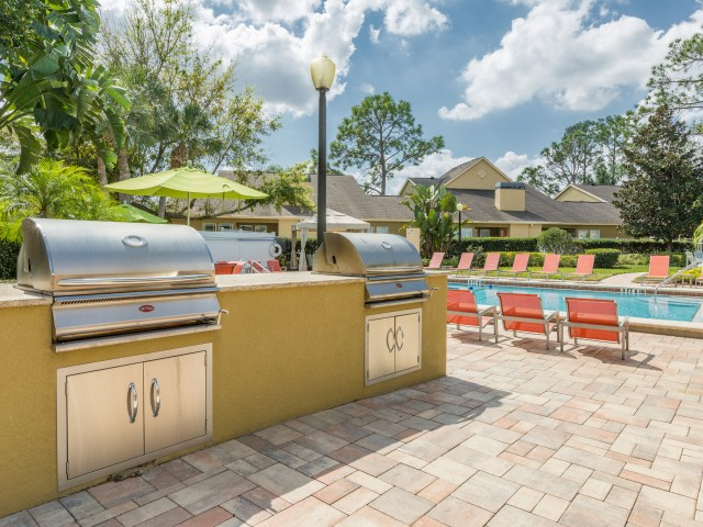 outdoor grilling station overlooking pool and lawn furniture
