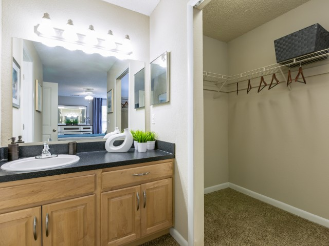 bathroom with vanity lights opening up to closet