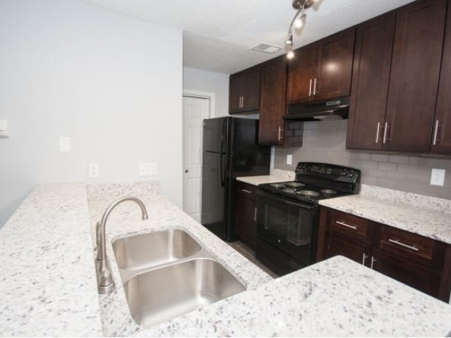 kitchen with white granite counters, black appliances with refrigerator and stove