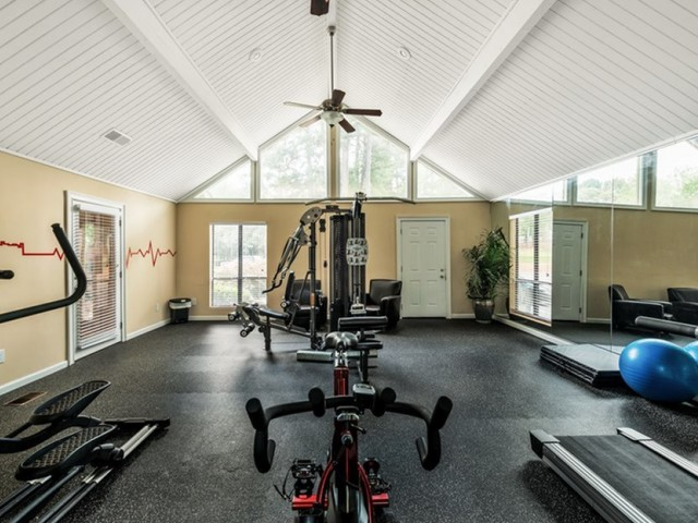 fitness center with a treadmill, stationary bike, elliptical, and universal weight machine