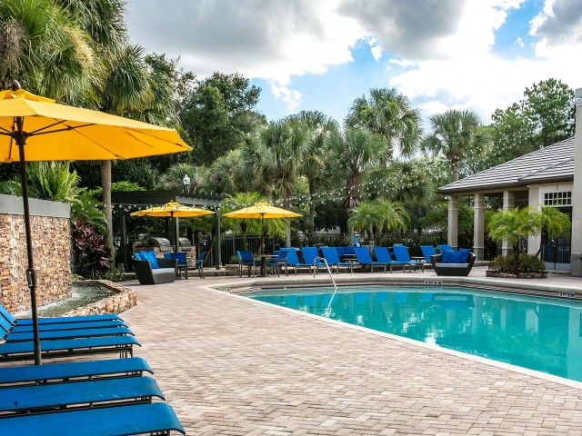 Alvista Metrowest Orlando Florida Pool Deck with swimming pool, paver surface, lounge chairs with cushions, umbrellas, water fountain and hanging lights next to the clubhouse with tropical landscaping