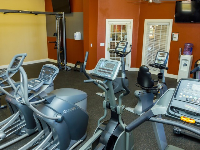 fitness center with stationary bikes and elliptical machines