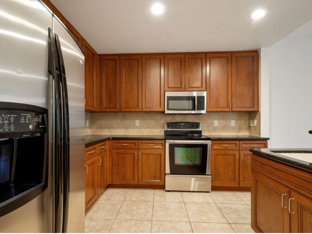 Kitchen with back splash, stainless steel refrigerator, microwave, and oven