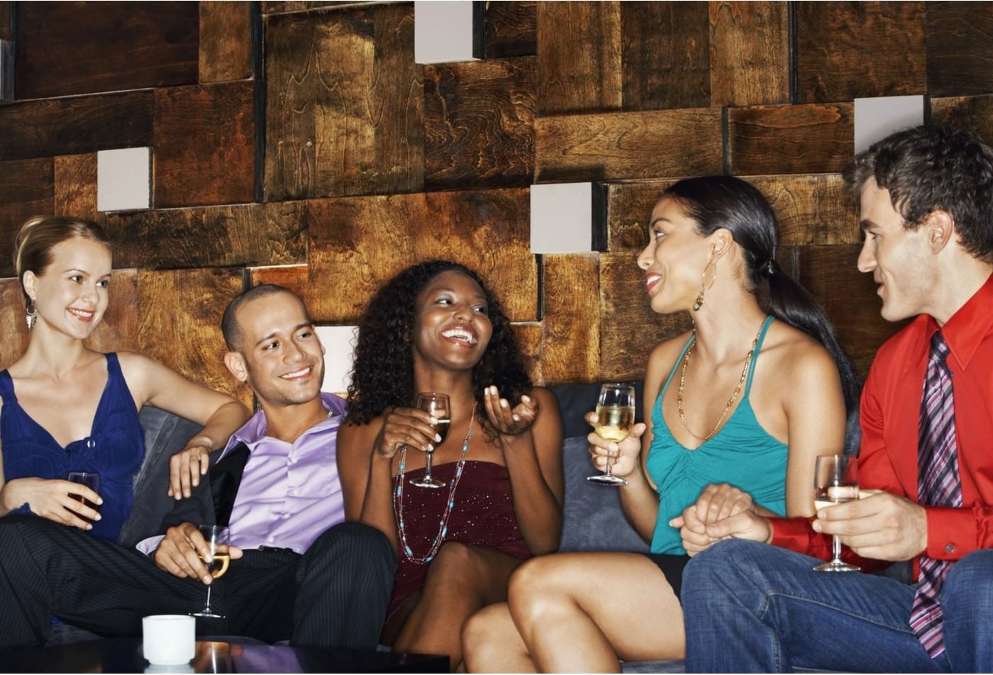 A group of couples enjoying the night out drinking wine and laughing .