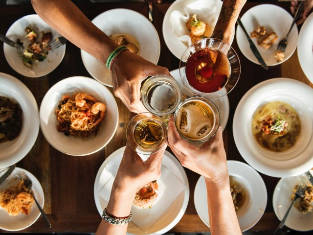 The Strand view of photo of four people toasting glasses over a dinner table