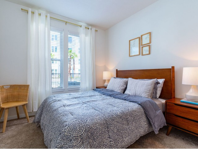 m2 at millenia bedroom with double window, queen size bed with end tables