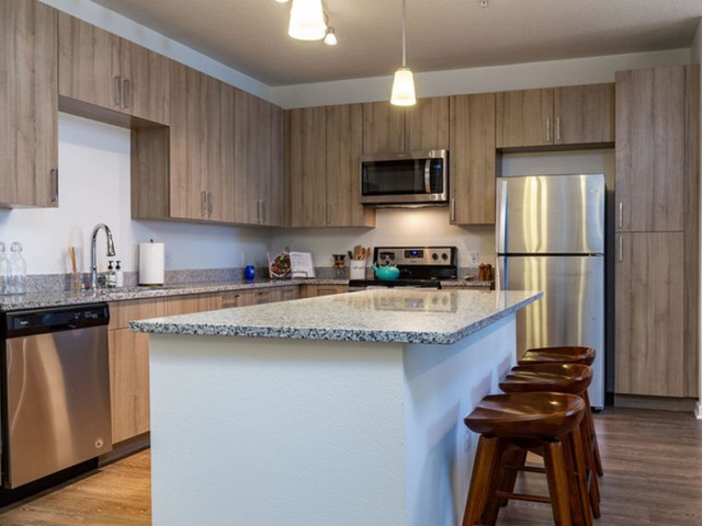 m2 at millenia island kitchen with stainless steel appliances, light wood cabinetry and island with seating