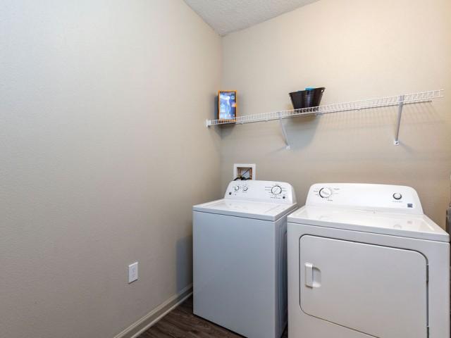 Tomoka Pointe Apartments Daytona Beach Florida large utility room with full size washer and dryer, wire rack shelf above