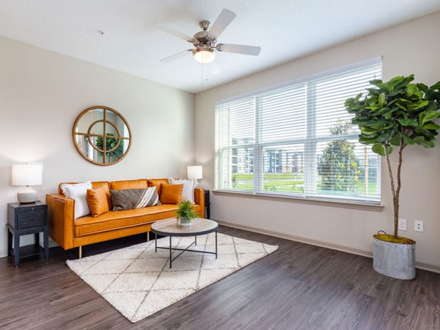 Tomoka Pointe Apartments Daytona Beach Florida furnished model apartment home living room with ceiling fan with light, triple window with blinds, wood vinyl plank flooring