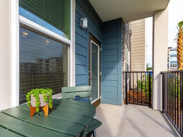 Tomoka Pointe Apartments Daytona Beach Florida exterior patio with metal railing, window and french door leading to apartment interior, exterior wall light