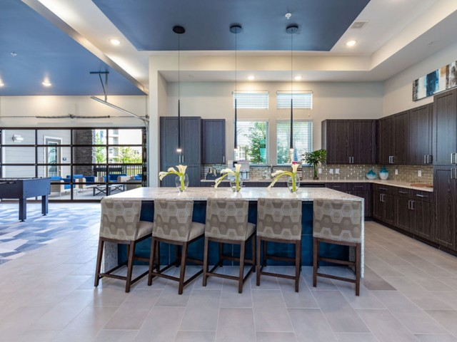 Tomoka Pointe Apartments Daytona Beach Florida clubhouse kitchen with wooden shaker cabinets, island kitchen with granite countertop, pendant lights, windows looking at pool area, tile flooring, adjacent to gaming table room with a glass ga