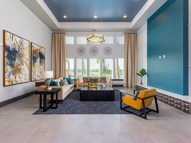 Tomoka Pointe Apartments Daytona Beach Florida living room style seating area in the clubhouse with couches, chair, end tables, coffee table, wall art, large decorative hanging light and large windows overlooking the parking lot