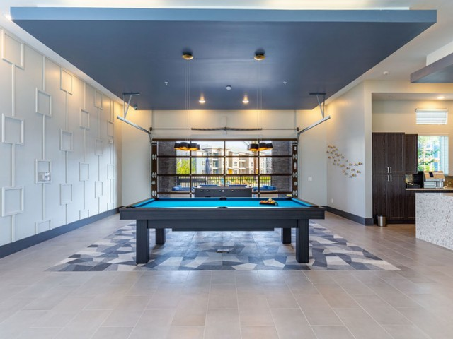 Tomoka Pointe Apartments Daytona Beach Florida clubhouse gaming room with billiards table and foosball table adjacent to clubhouse kitchen with glass garage door leading to the pool area