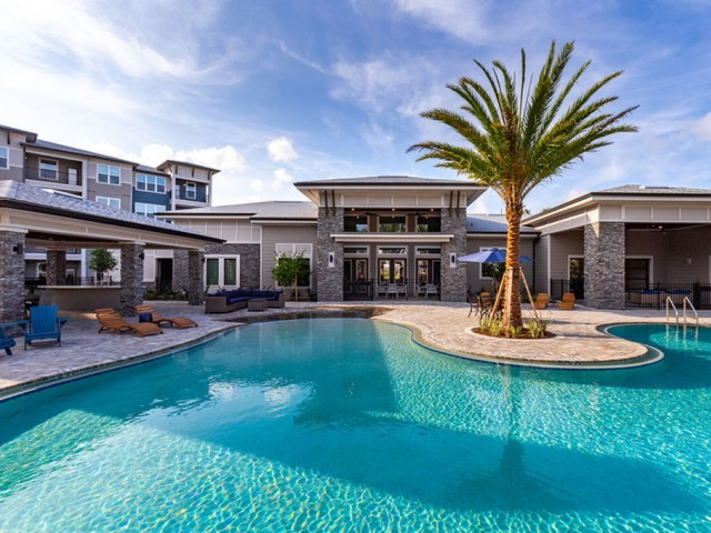 Tomoka Pointe Apartments Daytona Beach Florida pool with a poolside cabana, lounge chairs, clubhouse and a residential building adjacent