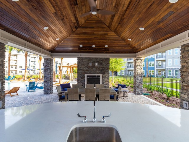 Tomoka Pointe Apartments Daytona Beach Florida outdoor pavilion with granite countertop wet bar, dining table and chairs, fireplace, open walls, wooden ceiling and ceiling fan