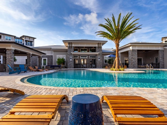 Tomoka Pointe Apartments Daytona Beach Florida outdoor swimming pool with loungers and tables, next to community clubhouse, tropical landscaping, outdoor kitchen building, residential building adjacent