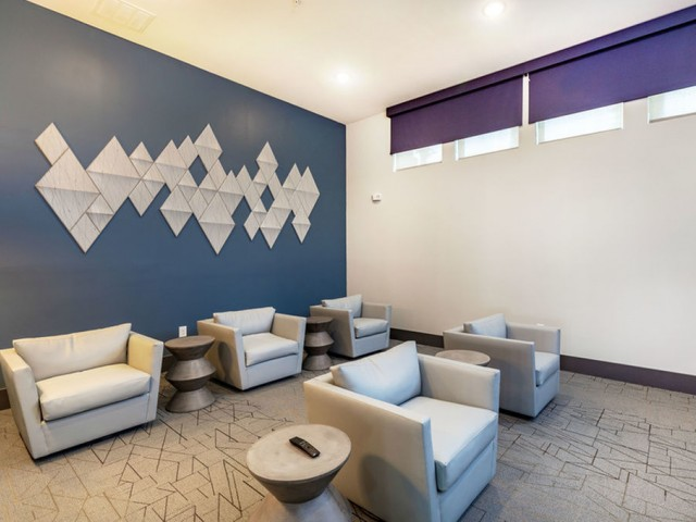 Tomoka Pointe Apartments Daytona Beach Florida media room with theater-style comfortable chairs with end tables, four windows with darkening shades, carpeted floors