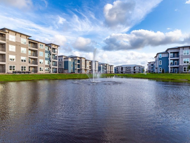 Tomoka Pointe Apartments Daytona Beach Florida community lake with fountain surrounded by residential buildings