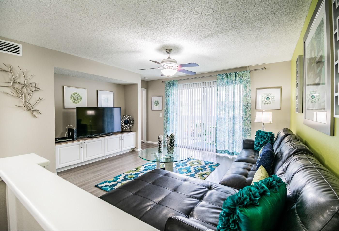 Furnished model living area with tv and decor