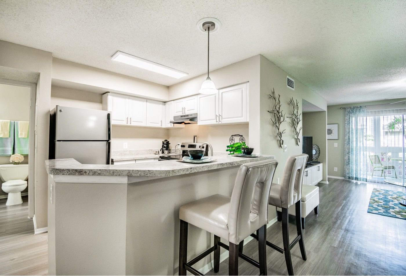 Furnished model kitchen area with bar and barstool seating and decor