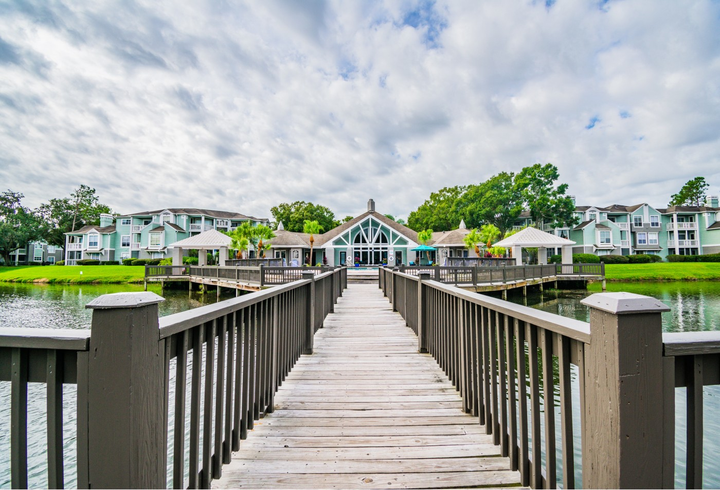 View of leasing office/club room and apartment building exterior from dock over lake