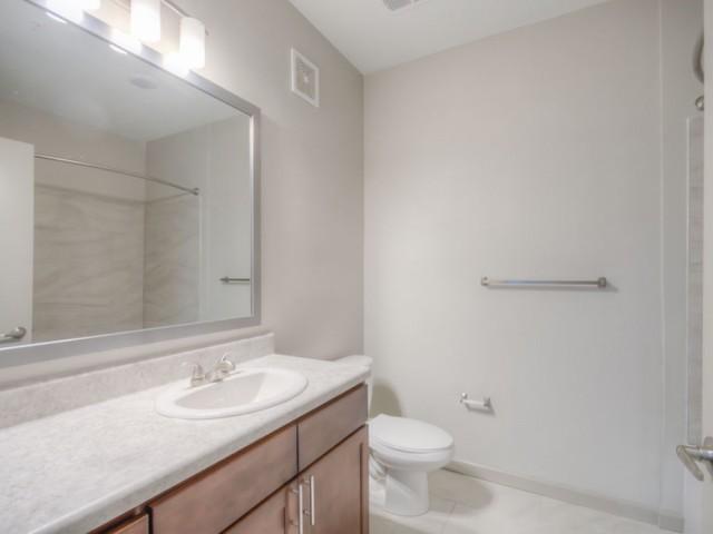 San Mateo Apartments Kissimmee Florida bathroom with large vanity, single sink, large mirror and light