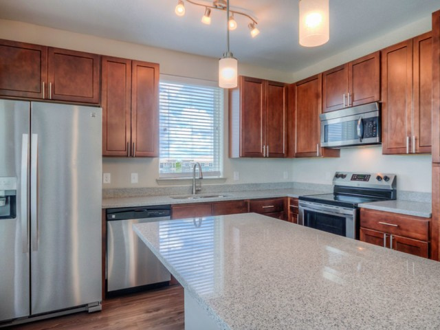 San Mateo Apartments Kissimmee Florida kitchen with wood cabinets, stainless steel appliances, granite countertop, window